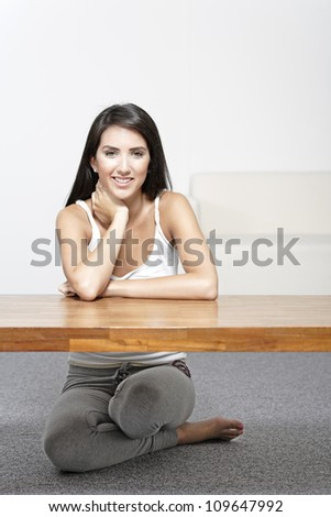 Beautiful young woman sitting next to a coffee table at home in casual clothes