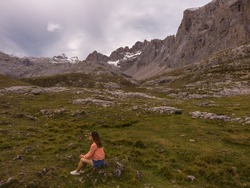 Beautiful young woman sitting next to stunning summits of Mounts Pena Remona, Torre de Salinas, La Padierna and Pico de San Carlos at Picos de Europa National Park, Spain.