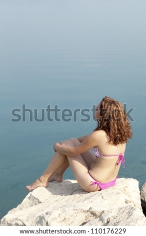 Beautiful young woman sitting on a beach and relaxing
