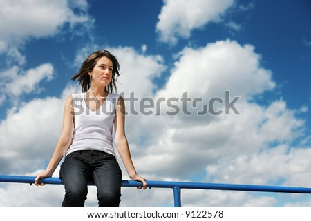 Beautiful young woman sitting on a border over cloudy blue sky.