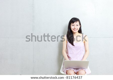 Beautiful young woman sitting on a chair with laptop computer.