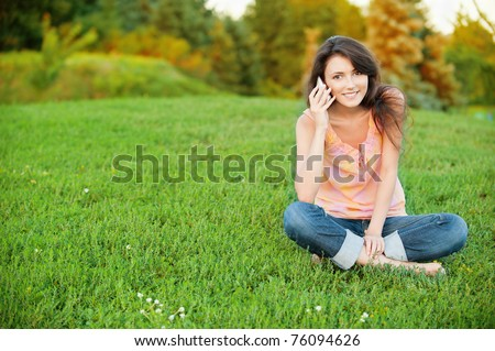 Beautiful young woman sitting on a green lawn in the lotus position and talking on a cell phone