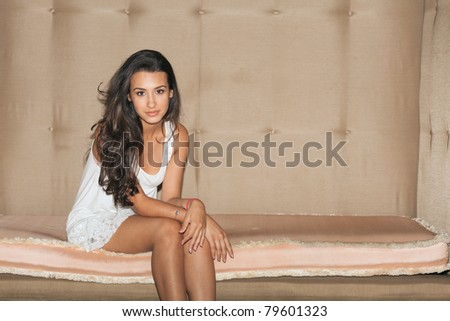 Beautiful young woman sitting on a large art deco sofa in a popular South Beach hotel in Miami Beach.