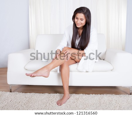 Beautiful young woman sitting on a sofa in her living room admiring her bare legs