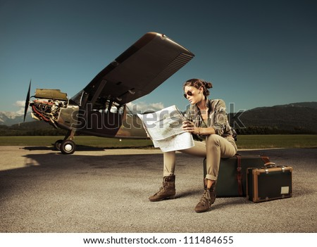 Beautiful young woman sitting on a suitcase, looks at a map. Airplane in the background