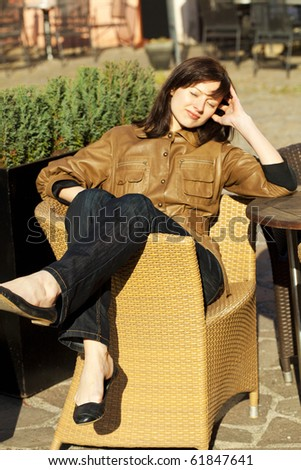 beautiful young woman sitting on a wicker chair