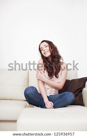 Beautiful young woman sitting on couch - stock photo