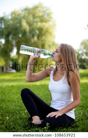 Beautiful young woman sitting on grass and drinking water at park