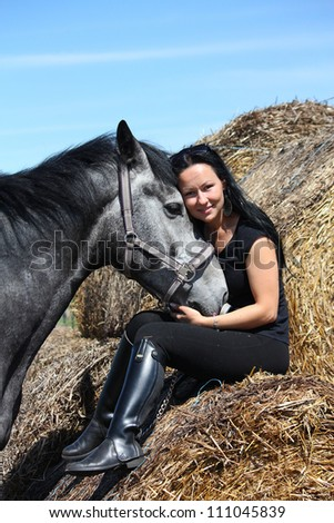 Beautiful young woman sitting on hay bale and dark gray horse