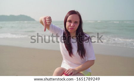 Beautiful young woman sitting on log and showing thumbs down. Brunette shows gesture of disapproval, sitting on log by sea or ocean in bright sunny day.