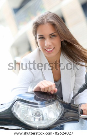 Beautiful young woman sitting on motorbike