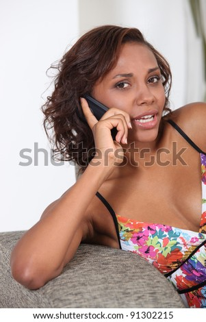 beautiful young woman sitting on the couch and talking on her cell