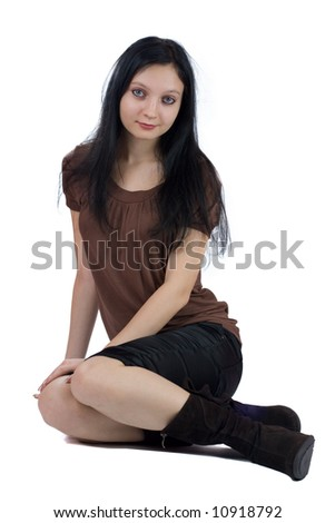 Beautiful young woman sitting on the floor isolated on white