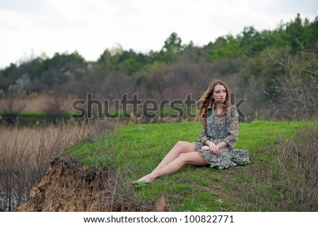 Beautiful young woman sitting on the grass (original)