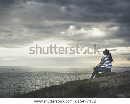 beautiful young woman sitting on the rocks by the sea and watching