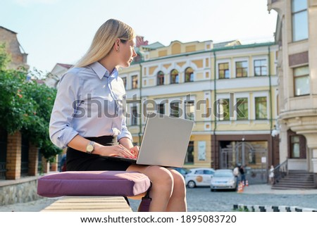 Beautiful young woman sitting outdoors using laptop, city street background. Female in business clothes, study, business, lifestyle concept stock photo