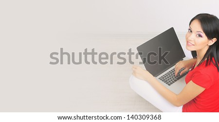 Beautiful young woman sitting with notebook in room