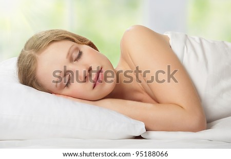 beautiful young woman sleeping in bed against the window with the green