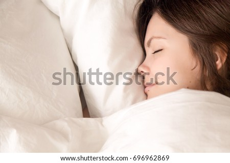 Beautiful young woman sleeping in cozy bed, attractive lady lying asleep on comfortable white luxury fresh linen, teenage girl enjoying healthy well sleep on soft pillow, close up headshot top view