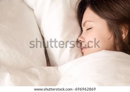Beautiful young woman sleeping in cozy bed, attractive lady lying asleep on comfortable white luxury fresh linen, teenage girl enjoying healthy well sleep on soft pillow, close up headshot top view