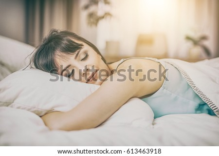 Beautiful young woman sleeping on a bed in the bedroom. A peaceful sleep makes you happy. #613463918