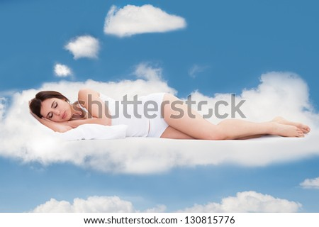 Beautiful Young Woman Sleeping On Clouds In Sky