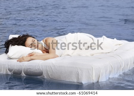 Beautiful young woman sleeping on the white bed in the sea