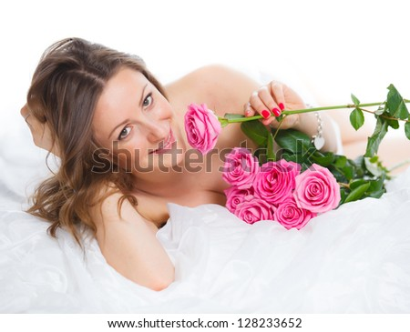 Beautiful young woman smelling a bunch of fresh roses