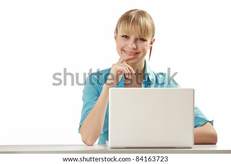 Beautiful young woman smiles while sitting at a laptop computer. Lots of copyspace