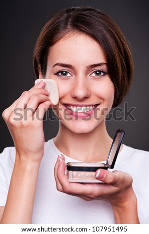 beautiful young woman smiling and applying powder on her skin. studio shot over dark background