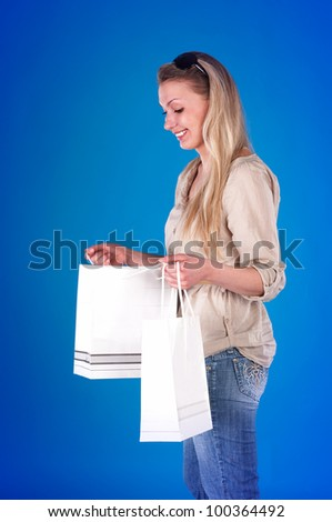 beautiful young woman smiling and looking into shopping bags against blue background