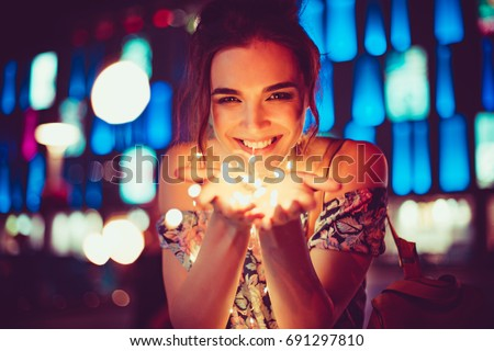 Beautiful young woman smiling and talking garlands of lights at city street