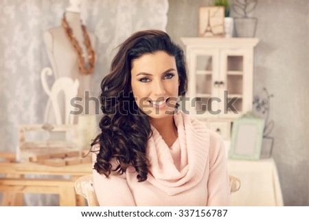 Beautiful young woman smiling at vintage home, looking at camera.