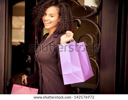 Beautiful young woman smiling holding colorful shopping bags