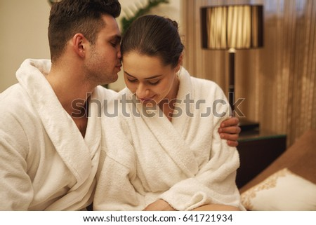 Beautiful young woman smiling joyfully while her man embracing her relaxing  together at spa center wearing · Beautiful young couple wearing toweling  robes ... 4a693b2c8
