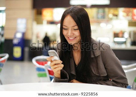 Beautiful young woman smiling looking at mobile phone. Shallow DOF.