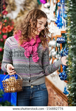 Beautiful young woman smiling while selecting Christmas ornaments in store - stock photo