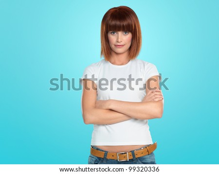 beautiful, young woman smiling with her arms crossed, on blue background