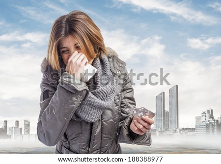 beautiful young woman sneezing and holding medicines