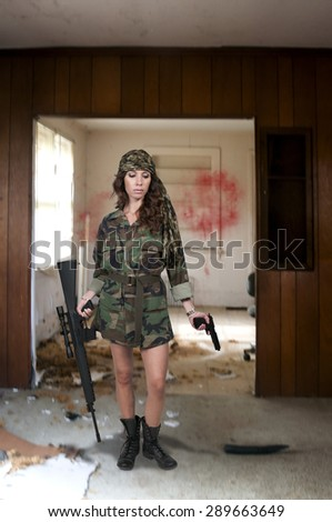 Beautiful young woman soldier with a M16 rifle and a pistol