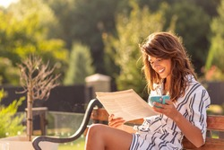Beautiful young woman spending sunny summer morning outdoors, having breakfast, reading newspaper and drinking coffee on the terrace in the backyard of her home