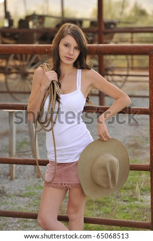 Beautiful young woman standing at corral fence with rustic leather lasso and cowboy hat on Southwestern Ranch.