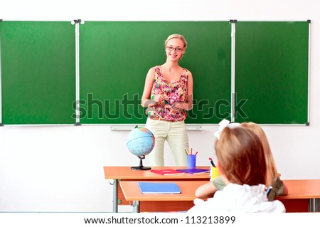 beautiful young woman standing at the blackboard and tells students a lesson