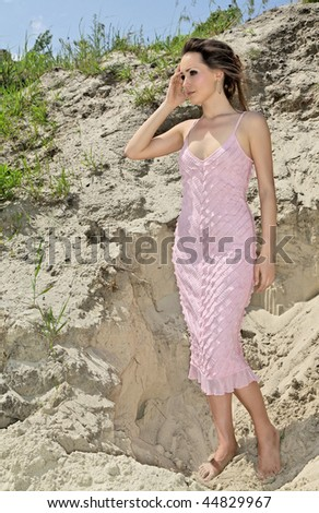 Beautiful young woman standing barefoot in sand quarry in a pink sundress