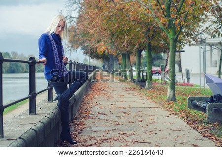 Beautiful young woman standing beside river on rainy autumn day.