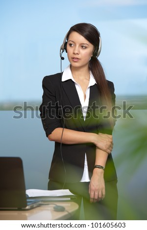 Beautiful young woman standing by desk