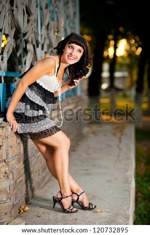 Beautiful young woman standing by wall on a summer day