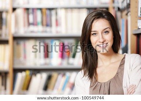 Beautiful young woman standing in library