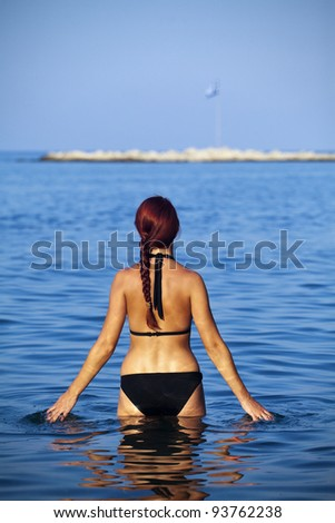 Beautiful young woman standing in sea. Rhodes during summer.