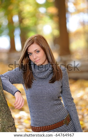 Beautiful young woman standing in tree with bright fall foliage as background